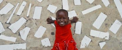 In an project volunteering with children in Tanzania a child smiles outside a care centre.
